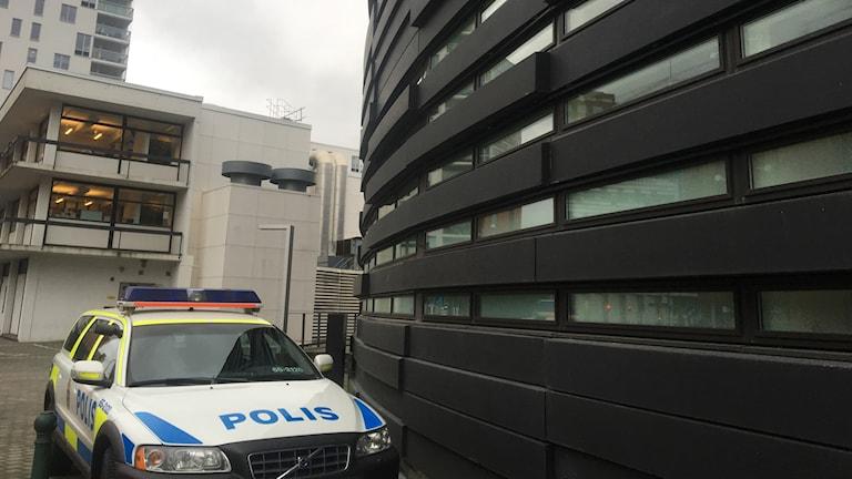 Polisbil intill byggnader