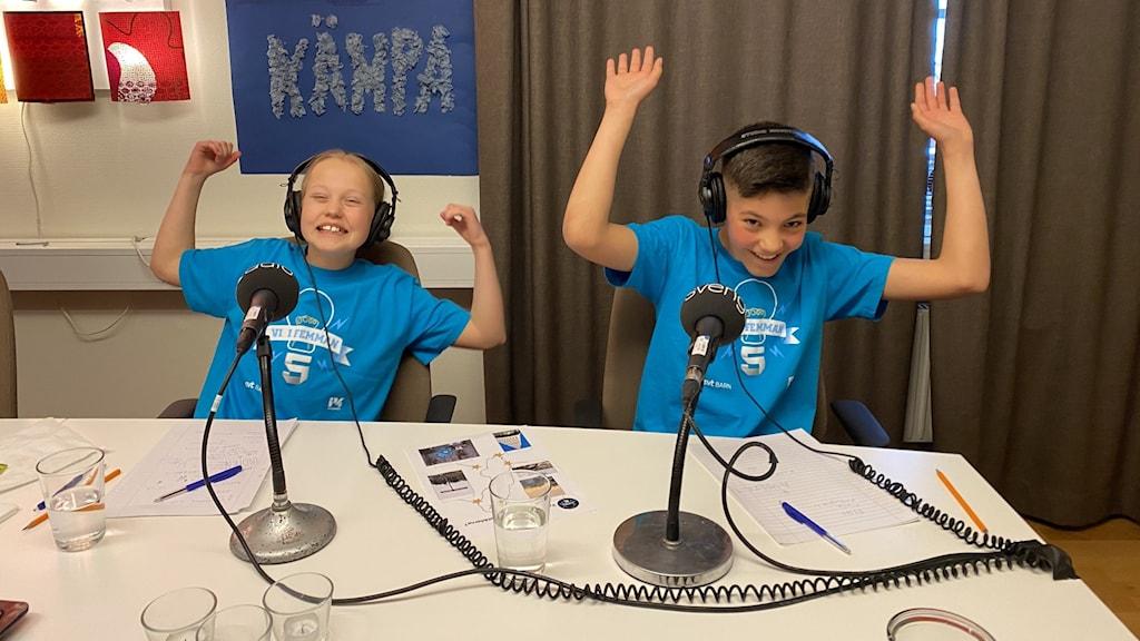Två barn i blåa t-shirts hurrar med uppsträckta armar.