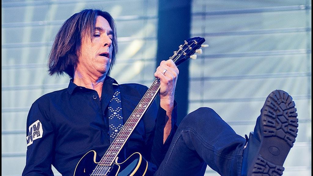 Man som spelar gitarr och lyfter ena benet.