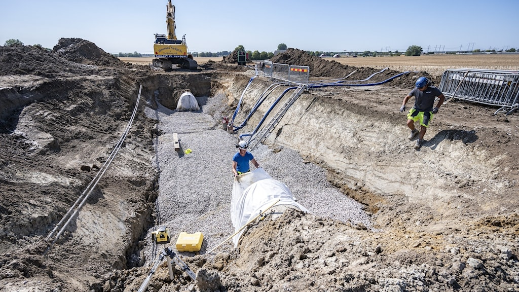 På bilden syns en frilagd vattenledning nära Vombverket i Skåne. En man står nere vid den framgrävda ledningen. En kollega är på väg ner till honom, ner för en slänt. Foto: Johan Nilsson/TT.