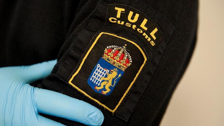 En tulltjänsteman visar upp tullemblemet på sin arm. Foto: Fredrik Sandberg/TT