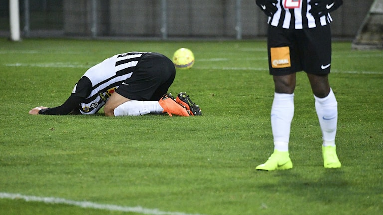 Fotbollsspelare ligger på planen och verkar ledsen.