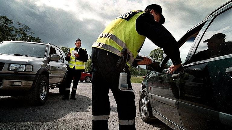 En polis kontrollerar en bil