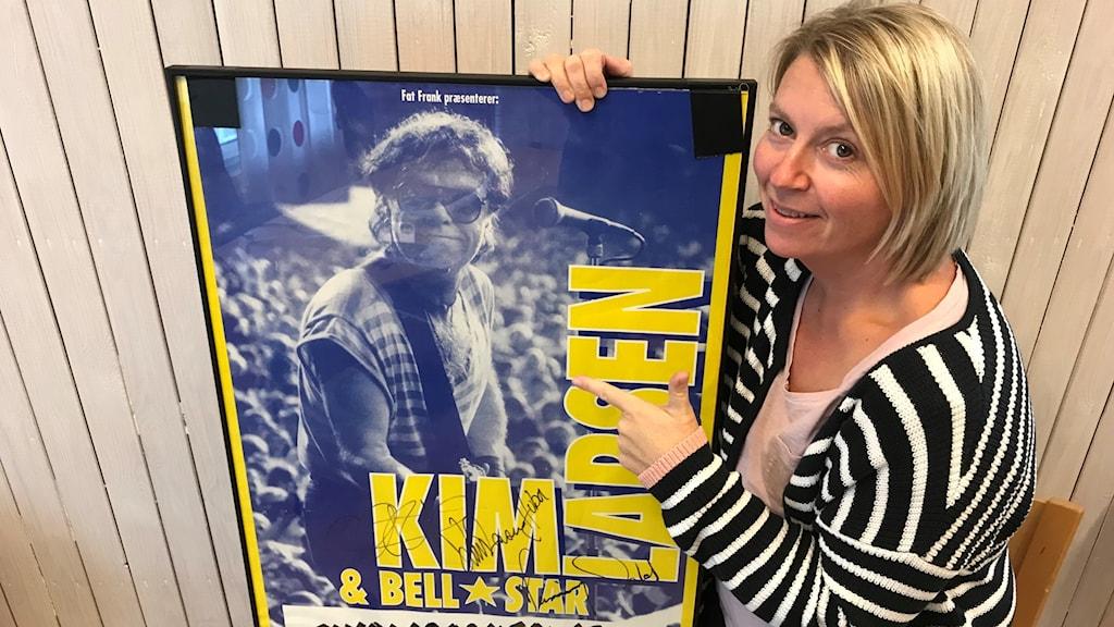 Kvinna som håller upp en affisch.