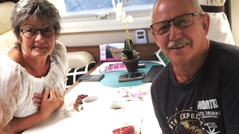 Kvinna och man vid bord i husbil.