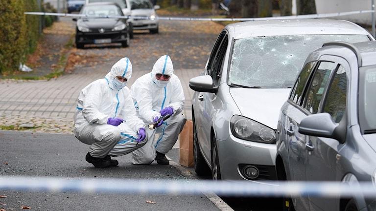 Tekniker undersöker en bil som utsatts för explosion.