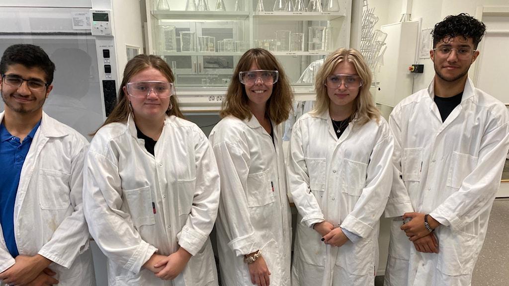 Fem personer i laboratorierockar.