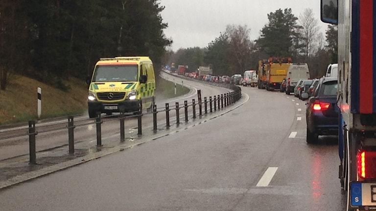 Ambulans på riksväg med bilköer.