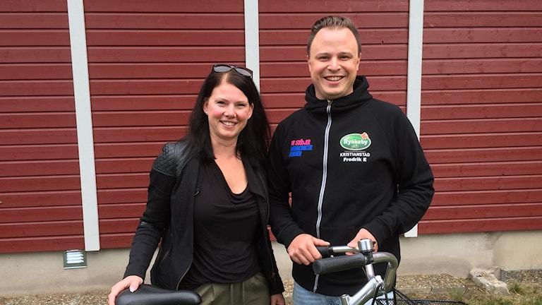 Kvinna och man som står bakom en cykel.