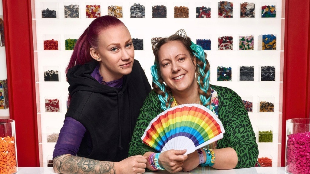 Två kvinnor står framför en vägg med legobitar