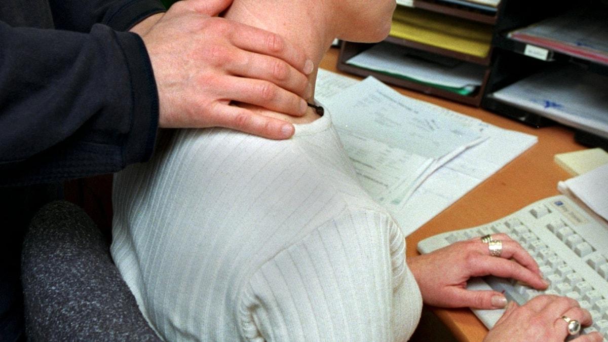 Manshand på en kvinnas nacke medan hon skriver på tangentbord