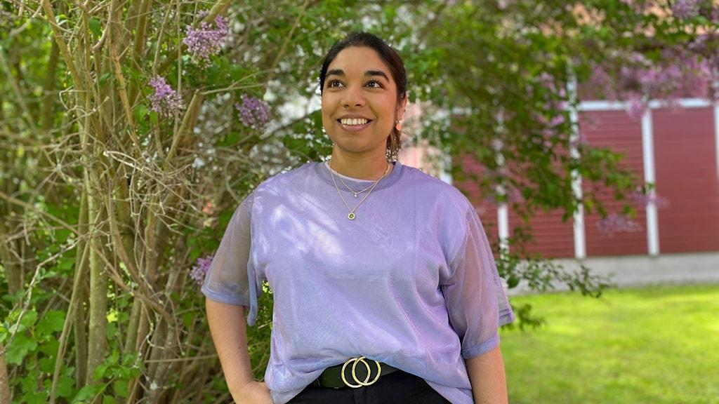Kvinna i lila tröja framför en syrénbuske