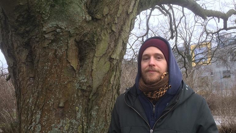 Man med mössa och luva står under ett träd.