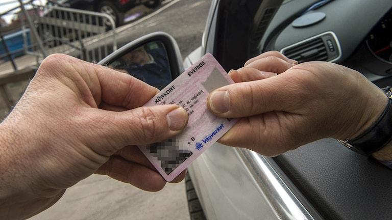 två händer som håller ett körkort. Den ena sitter i en bil.