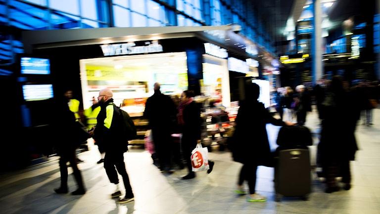 Personer i en stationsbyggnad.