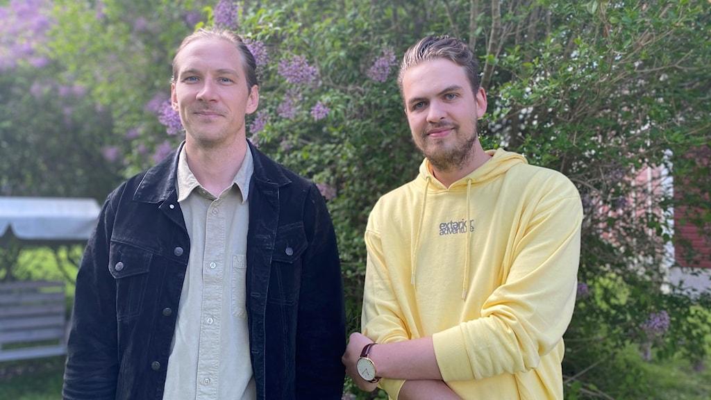Två män som står utomhus, med en grön buske i bakgrunden. Till höger står en man med svart jacka, och till vänster en man med gul hoodie.
