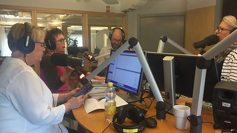 Tre kvinnor och en man står runt ett studiobord i en radiostudio med mikrofoner framför sina ansikten.
