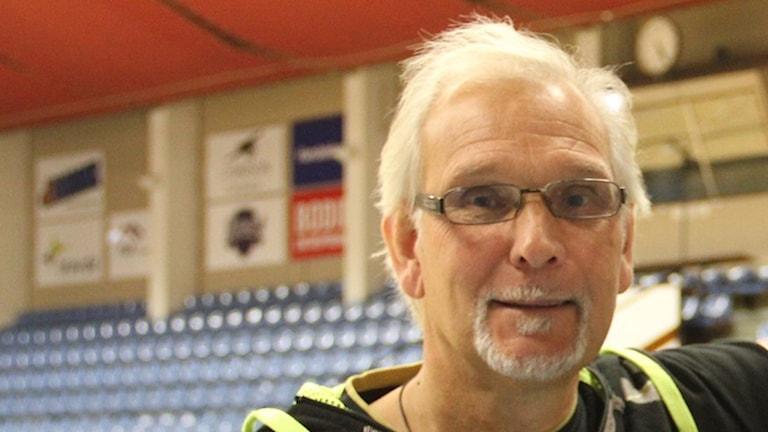 Vithårig man med lite skägg och glasögon tittar in kameran. Befinner sig i en idrottsarena.