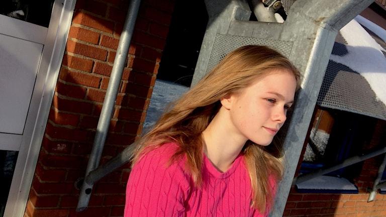 En tjej i rosa tröja står lutat mot en pelare.