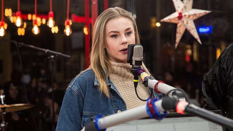 Blond kvinna står bakom mikrofon