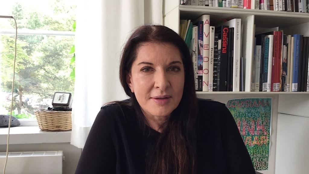 Kvinna med långt mörkt hår sitter framför ett fönster och en bokhylla.