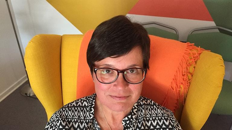 Mörk- och korthårig kvinna med glasögon som sitter i en gul fåtölj.