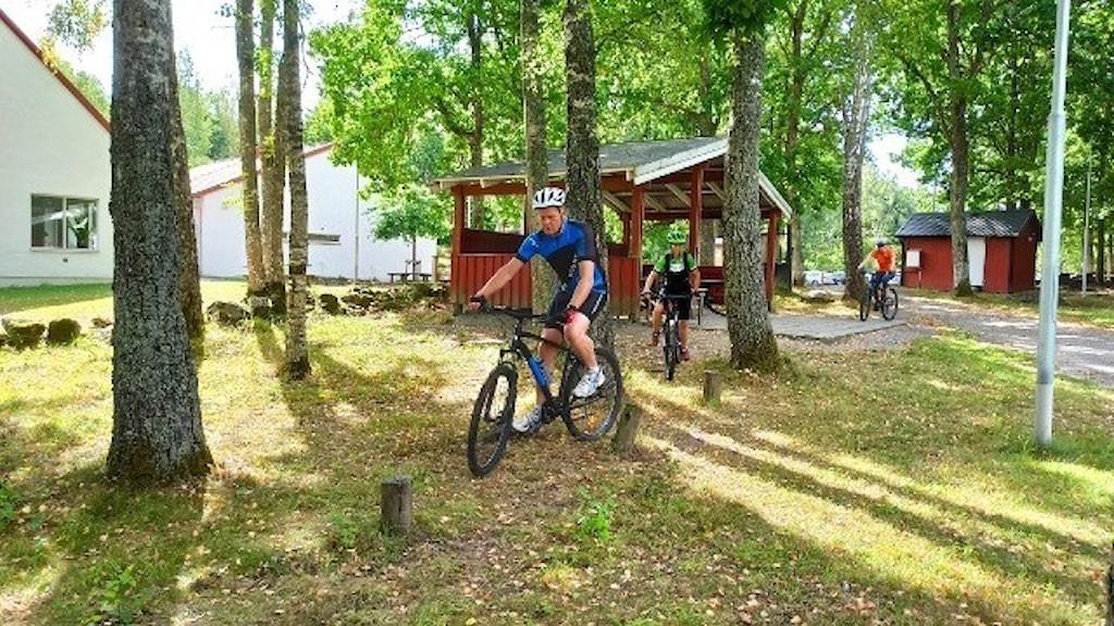 Man cyklar först i led. Skogsmiljö i bakgrunden.