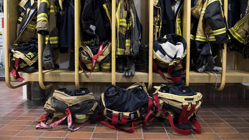 Ett omklädningsrum på en brandstation med fack fulla med larmställ.