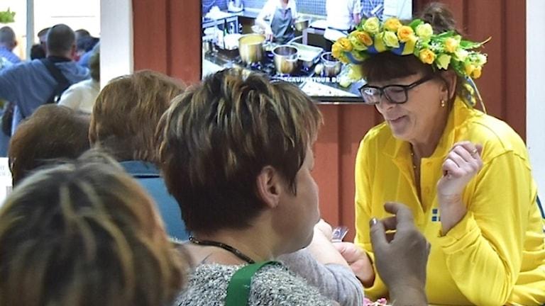 Helena Ingvarsson i midsommarkrans och gul skjorta