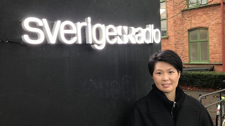 Kvinna vid Sveriges Radio-skylt.