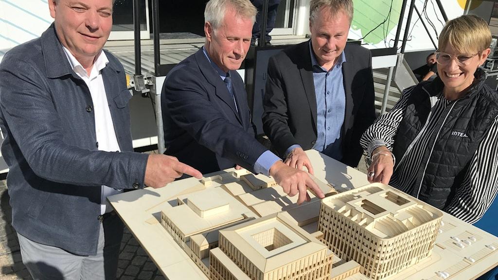 Tre män och en kvinna pekar på en byggprototyp