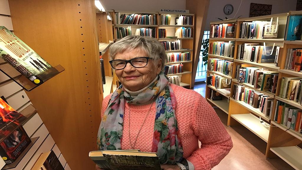 Äldre kvinna står i rosa tröja bland bokhyllor.