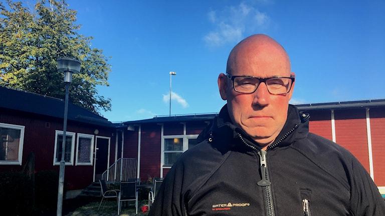 Man som står framför ett rött hus