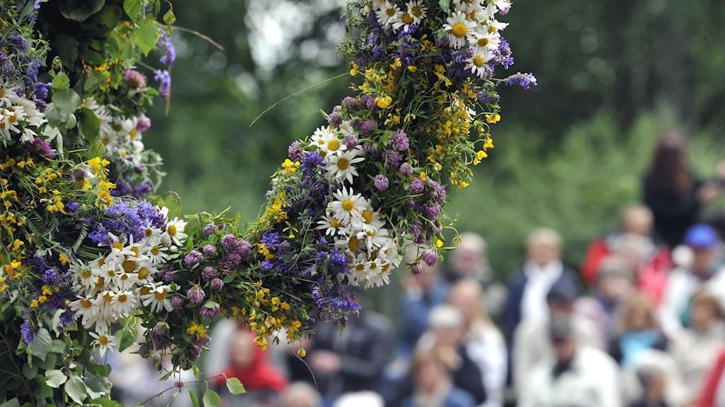 Blomsterkrans på midsommarstång och folk i bakgrunden utomhus