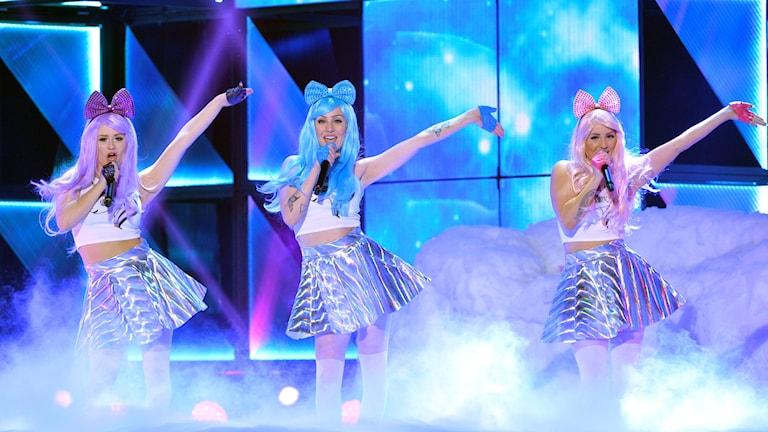 Tre kvinnor med pastellfärgade rosetter i håret som står på en scen.