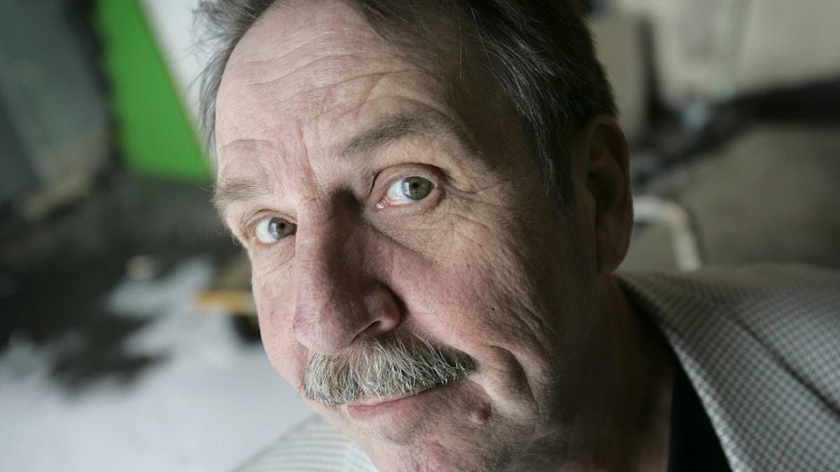 Porträtt på äldre man med mustasch.