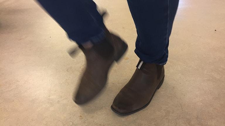 Fötter med skor på som trampar på ett golv.