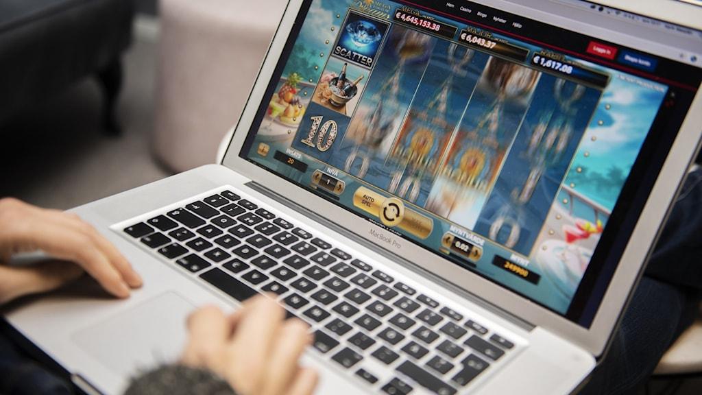 datorskärm där ett onlinekasinospel syns på skärmen. en persons händer rör sig över tangenterna.