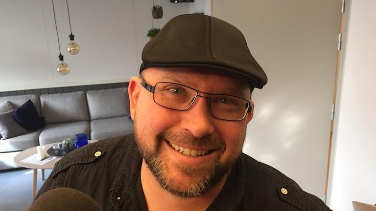 Man med keps, skägg och glasögon tittar in i kameran från en studio.