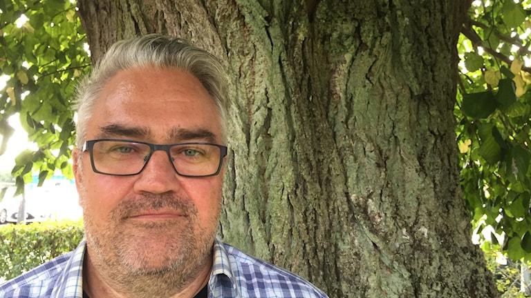 Man med glasögon som står framför ett träd.