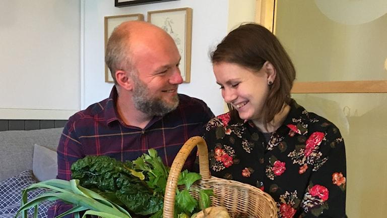 Ett par med en korg grönsaker.