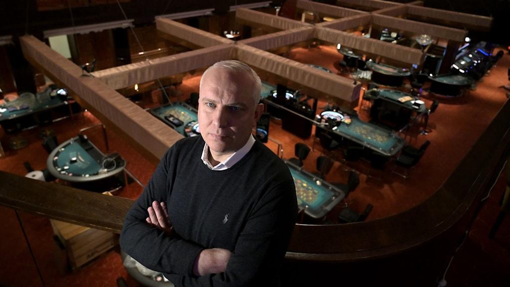 Man med armarna i kors med en casinomiljö bakom sig.