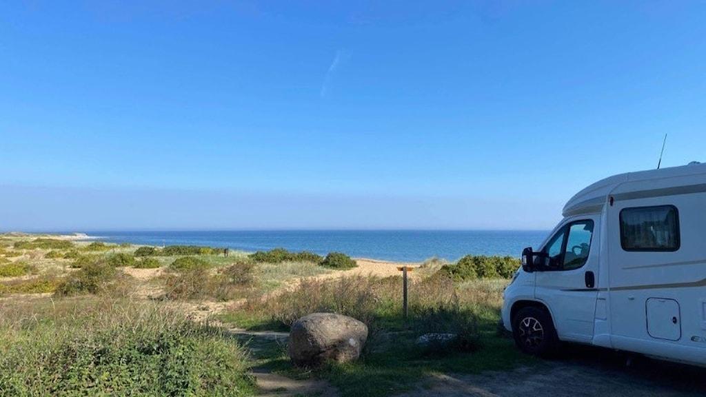 En husbil står vid en fin strand.