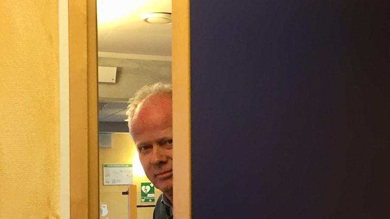Man som tittar fram bakom en dörr.