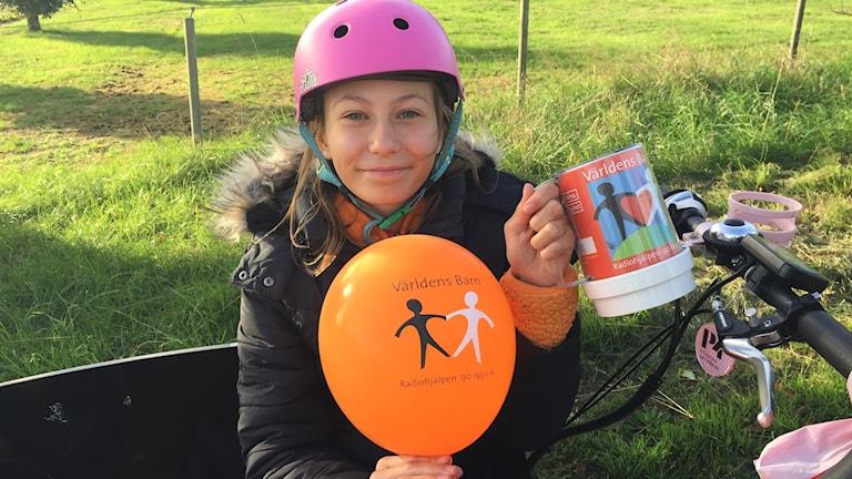 Flicka med cykelhjälm, ballong och insamlingsbössa.