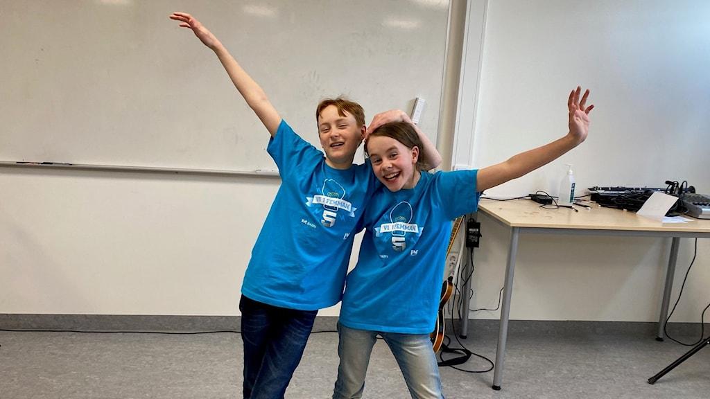 Två barn i blåa t-shirts som håller om varandra och ser glada ut.