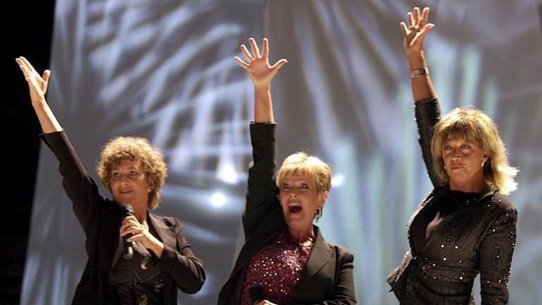 Tre kvinnor sträcker upp en av sina armar i luften. Det står på en scen.