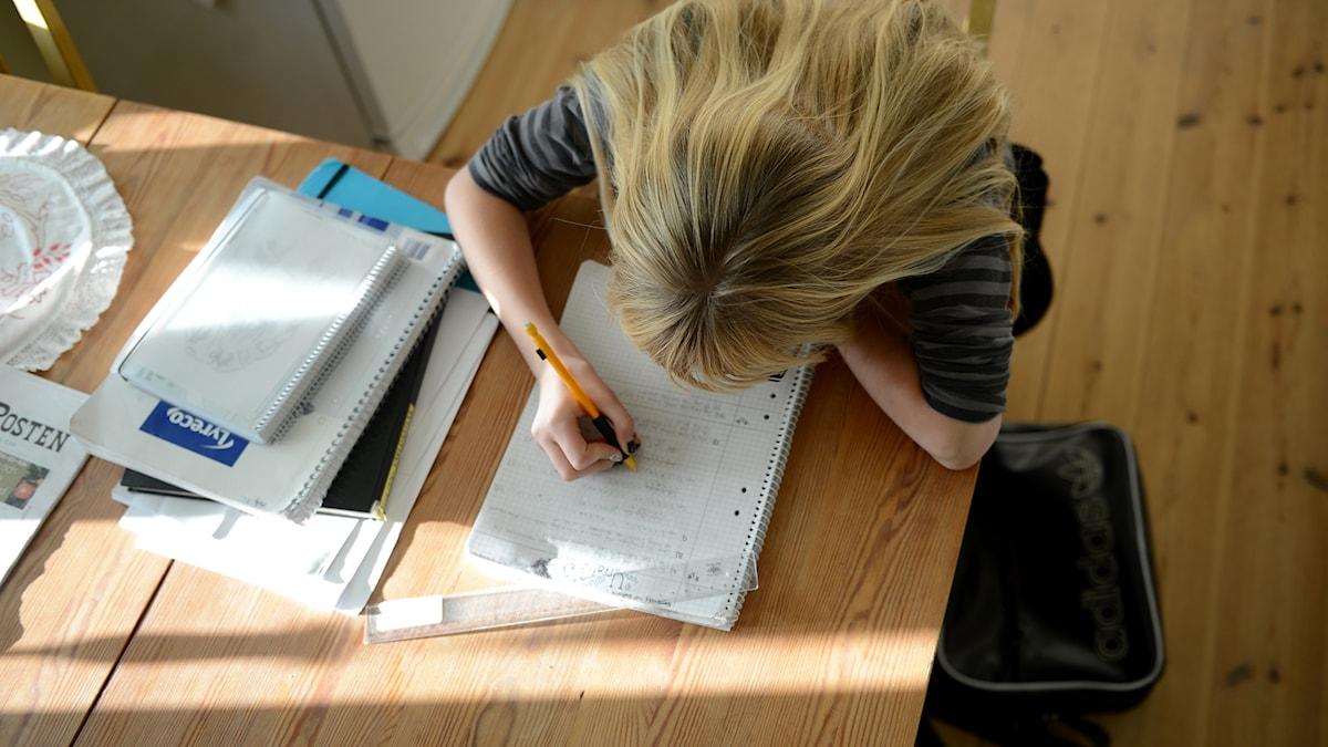 kvinna som skriver anteckningar/studerar
