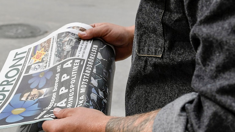 Man som håller i en tidning.