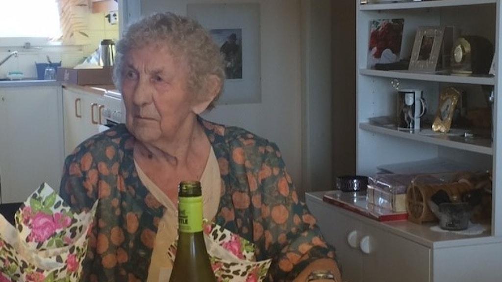 Äldre kvinna som tittar allvarligt åt sidan.